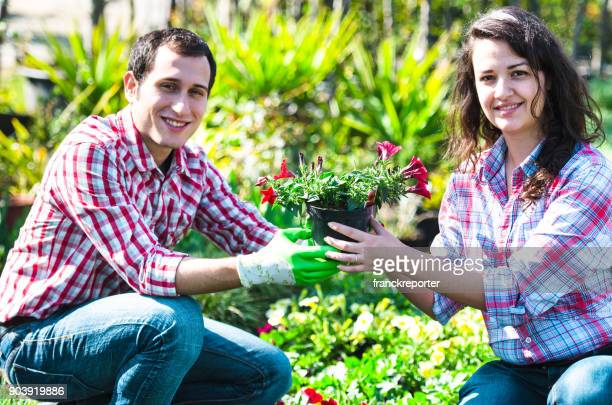 happy couple of florist holding a plant