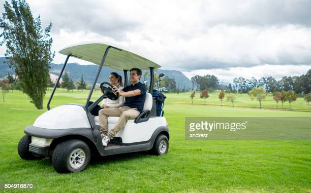 Happy couple of golfers driving a golf cart