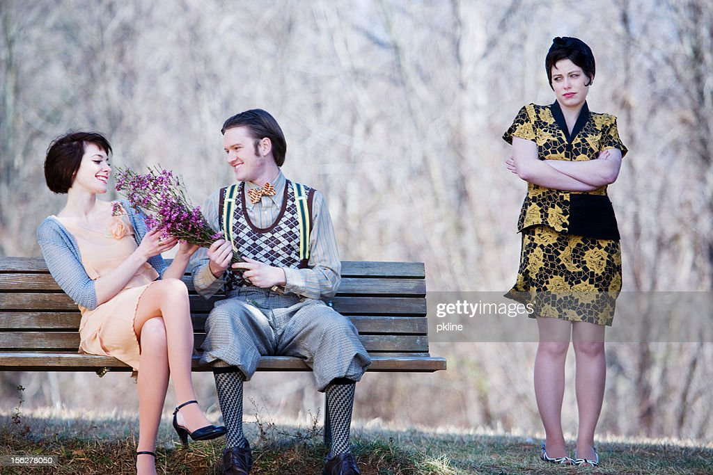 Happy couple on a bench while jealous lady watches : Stock Photo