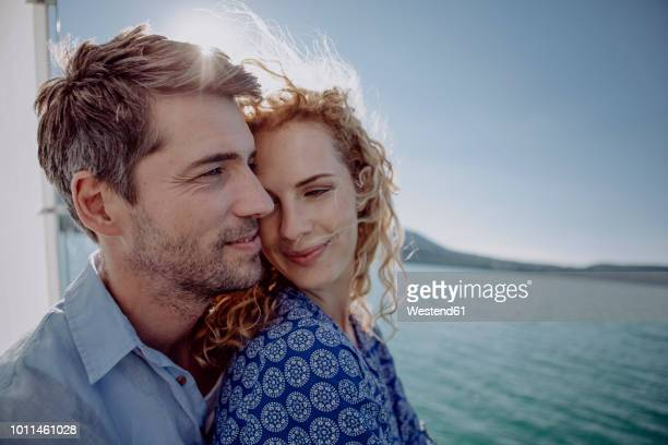 happy couple on a sailing boat - mid adult couple stock pictures, royalty-free photos & images