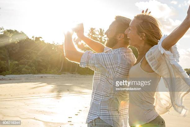 Happy couple on beach at sunset take selfie portrait