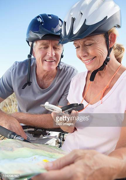 Happy couple on bicycle looking at map using GPS