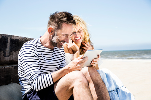 Happy couple on the beach looking at tablet - gettyimageskorea