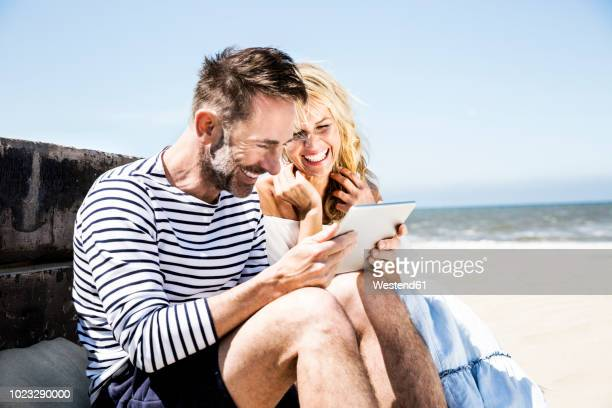 happy couple on the beach looking at tablet - heterosexual couple photos - fotografias e filmes do acervo