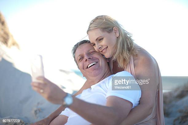happy couple on the beach taking a selfie - fat man on beach stock photos and pictures