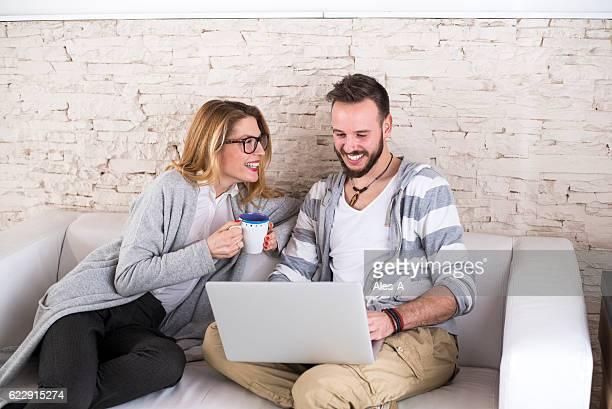 Happy couple on white sofa using laptop