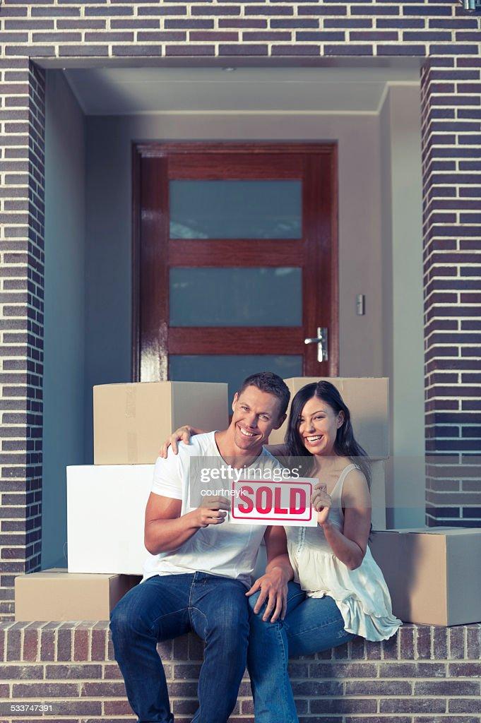 Coppia felice al di fuori di una casa con scatole in movimento. : Foto stock