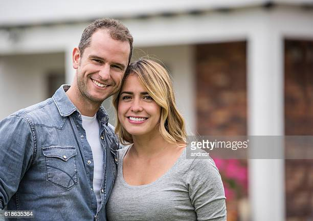Happy couple outside their house