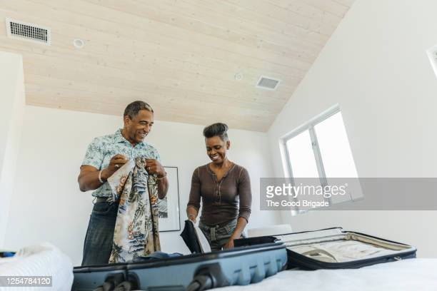 happy couple packing suitcase for vacation - holiday stock pictures, royalty-free photos & images