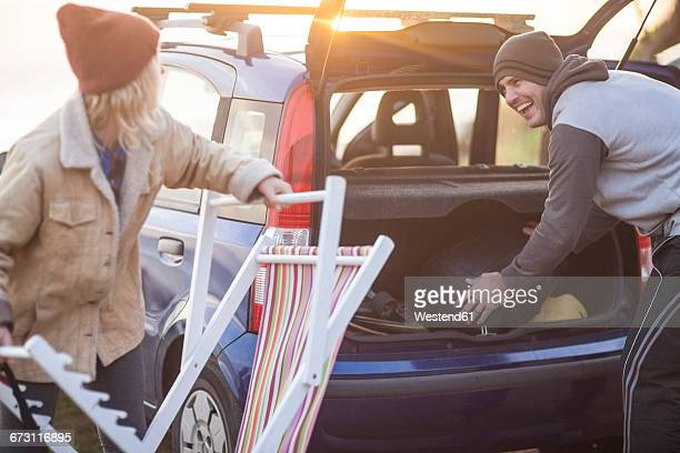 Happy couple packing their items in the car at sunset
