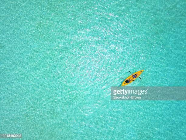 happy couple paddling their kayak through the clear tropical water in maldives. aerial, look down - カヌー ストックフォトと画像