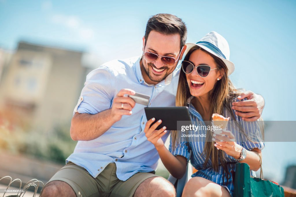 Happy couple paying on line with credit card and digital tablet on the street : Stock Photo