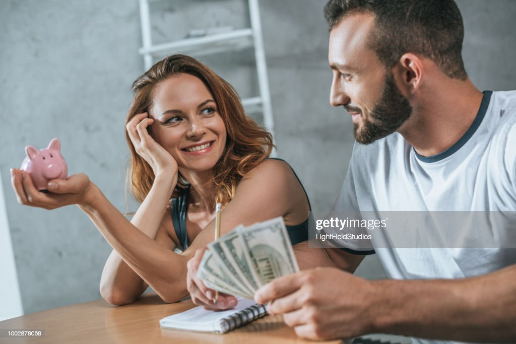 happy couple planning family budget and looking at each other in living room : Stock Photo