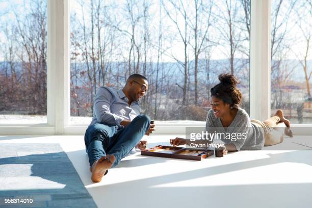 Happy couple playing backgammon at home