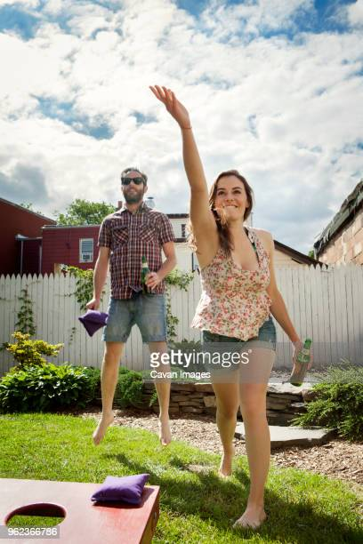 Happy couple playing bean bag toss game in lawn
