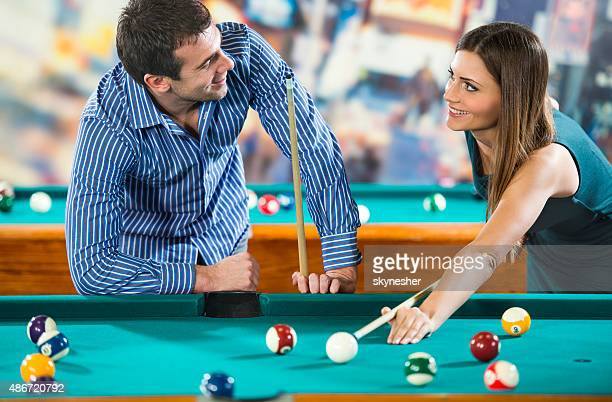 Happy couple playing billiard and communicating.