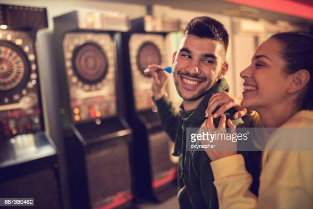 Happy couple playing darts in a pub and having fun together.