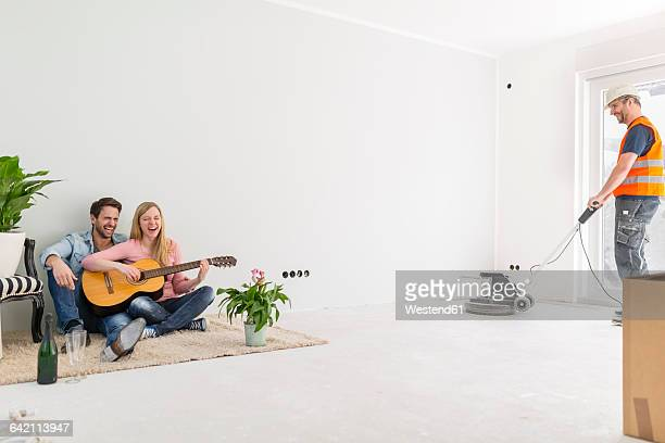 Happy couple playing guitar and singing at their new home while