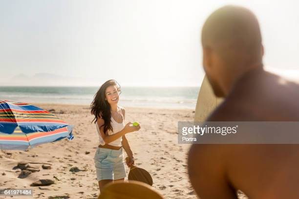 Happy couple playing table tennis at beach