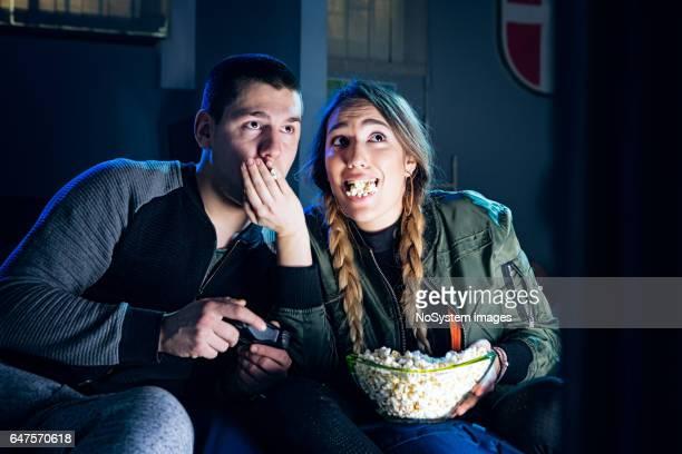 gelukkige paar spelen van videospellen en plezier samen eten popcorn - vriendje stockfoto's en -beelden
