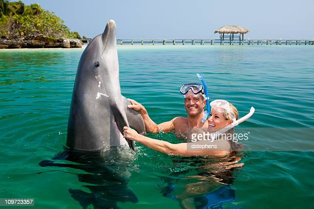 Happy couple playing with dolphin in tropical sea