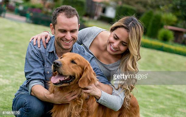 Happy couple playing with their dog outdoors