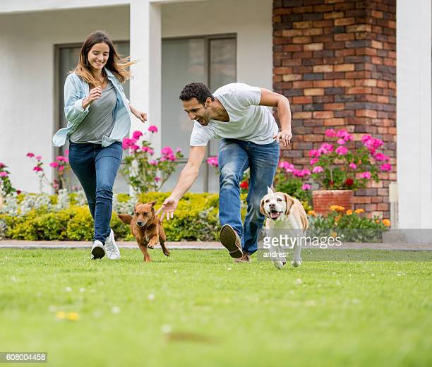 Happy couple playing with their dogs