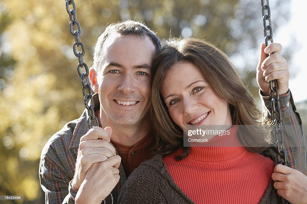 Happy couple posing together on swing : Stockfoto