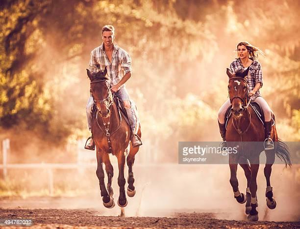 Heureux couple en pratiquant avec leurs chevaux dans la nature.