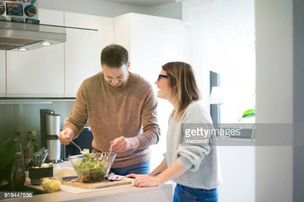 Happy couple preparing salad in kitchen together