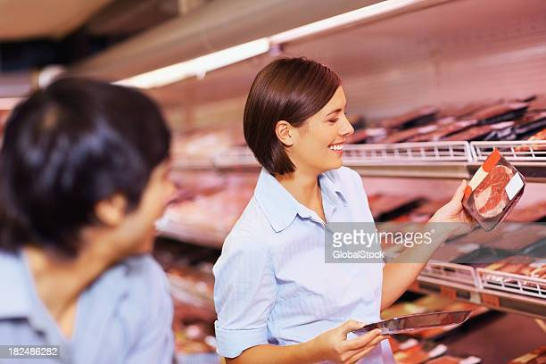 Glückliches Paar, die ein Paket von Fleisch im Supermarkt