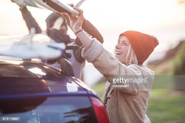 Happy couple putting surfboard on car roof at sunset