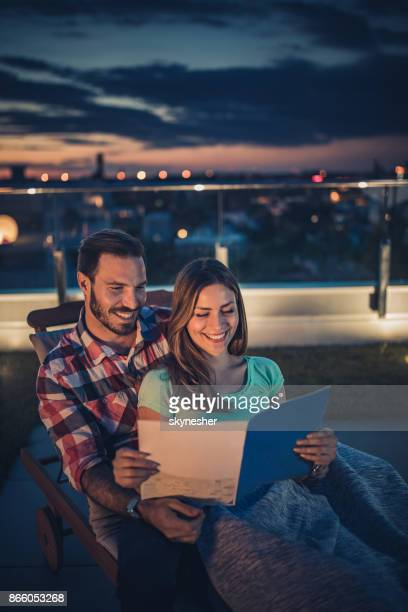 happy couple reading a magazine on deck chair at penthouse terrace by night. - penthouse magazine photos stock pictures, royalty-free photos & images