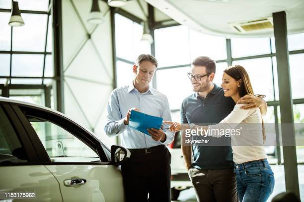 happy couple reading buying plan with car salesperson in a showroom. - car dealership stock pictures, royalty-free photos & images
