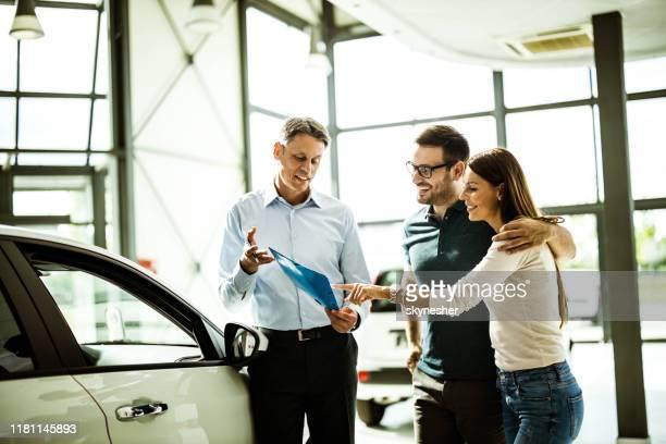ショールームで車の販売員と購入計画を読んで幸せなカップル。 - ショールーム ストックフォトと画像