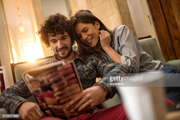 Happy couple reading magazine together at home.