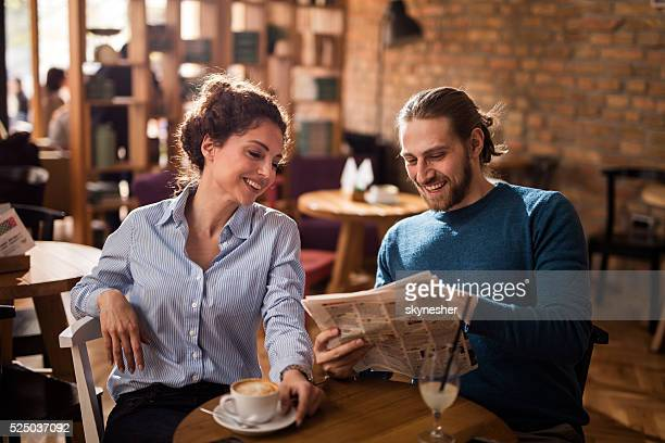 Happy couple reading newspaper in a cafe.