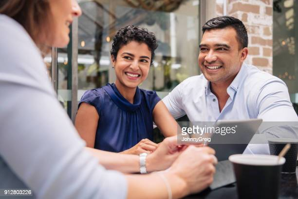happy couple receive good news from professional businesswoman - financial advisor stock pictures, royalty-free photos & images