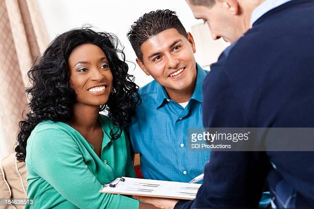 Happy couple receiving advice from financial counselor