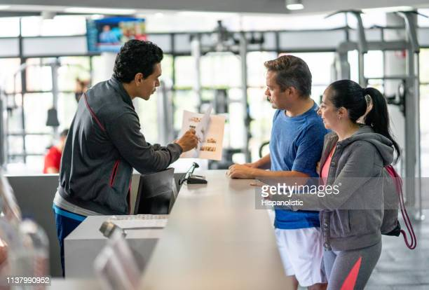 happy couple registering at the gym while employee explains benefits showing them a catalogue - organized group stock pictures, royalty-free photos & images