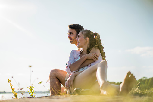 Happy couple relaxing at the riverside in summer - gettyimageskorea