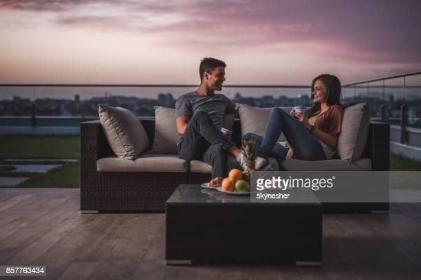 Feliz pareja relajarse en un patio en el crepúsculo y comunicación.