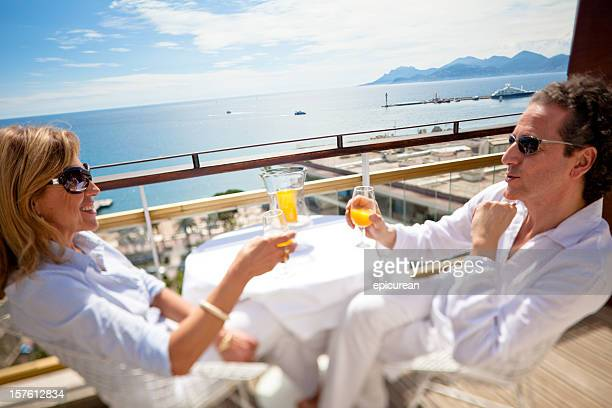 happy couple relaxing on a penthouse balcony - central europe stock photos and pictures