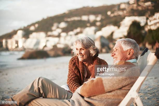 happy couple relaxing on chairs at beach - retirement stock pictures, royalty-free photos & images