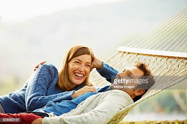 happy couple relaxing on hammock - 40 49 jaar stockfoto's en -beelden