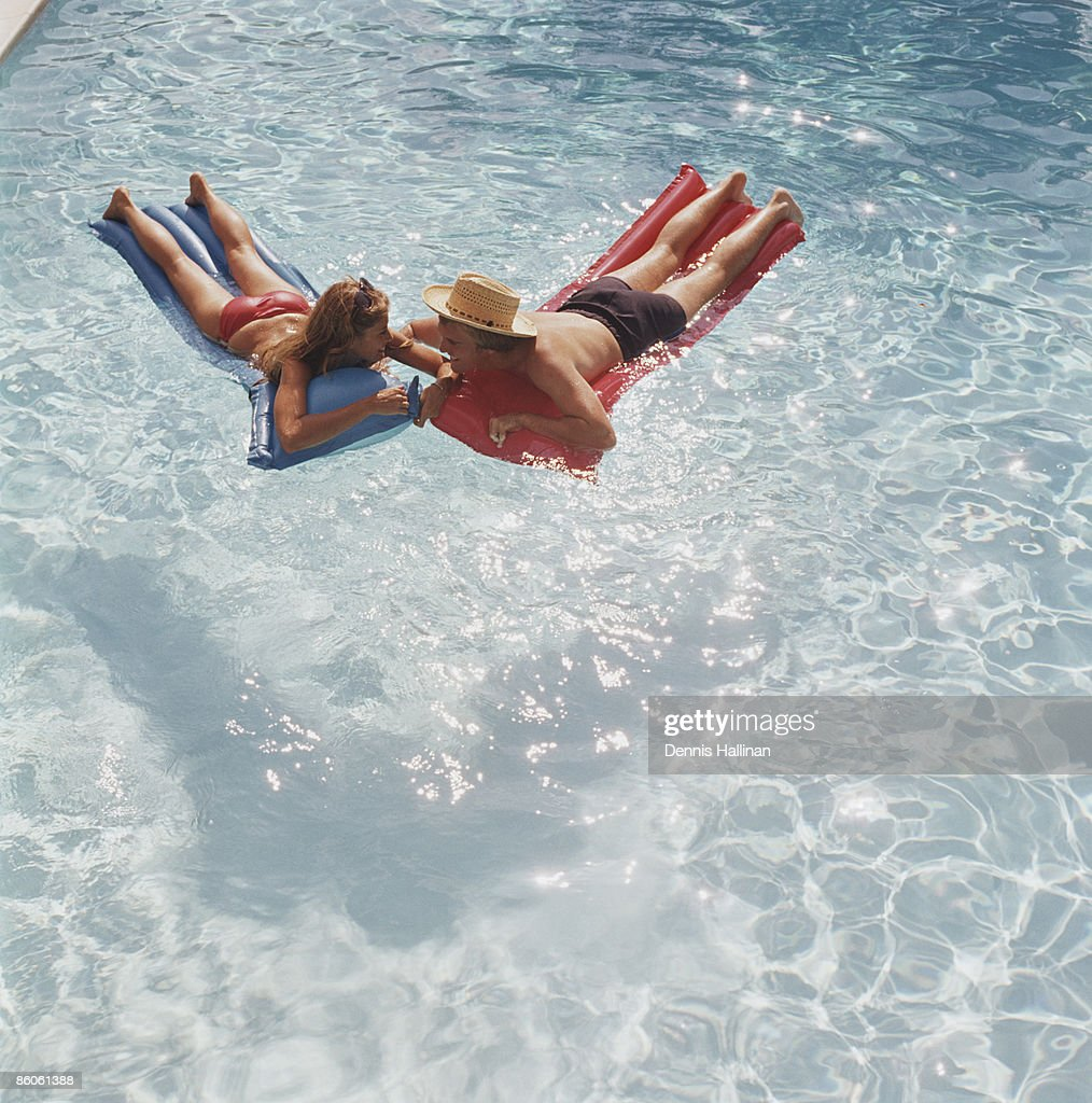 Happy Couple Relaxing On Inflatable Pool Rafts : Stock Photo