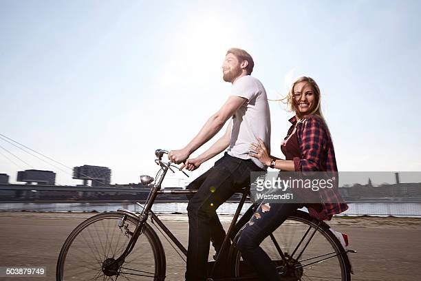 happy couple riding bicycle on riverbank - riverbank stock photos and pictures