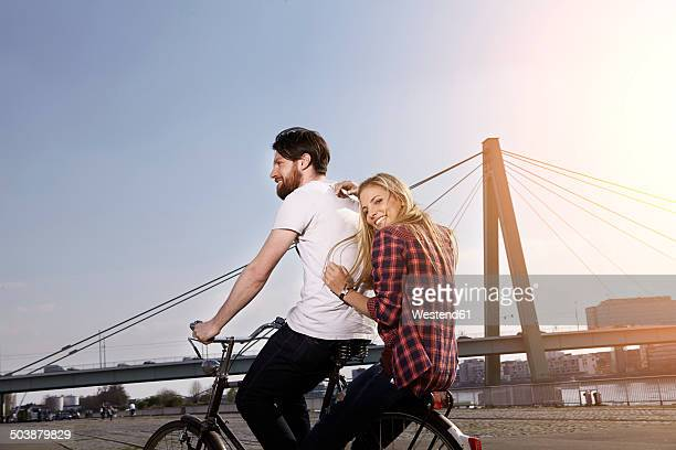 Happy couple riding bicycle on riverbank