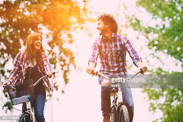 Glückliches Paar Reiten Fahrräder zusammen.