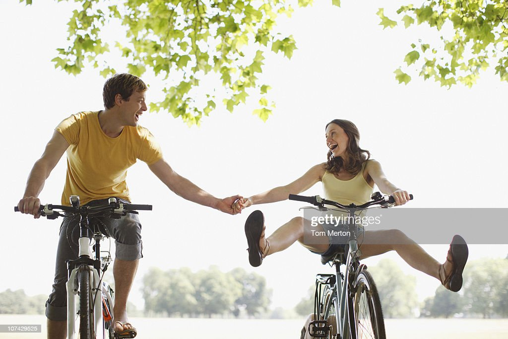 Happy couple riding bicycles and holding hands : Stock Photo